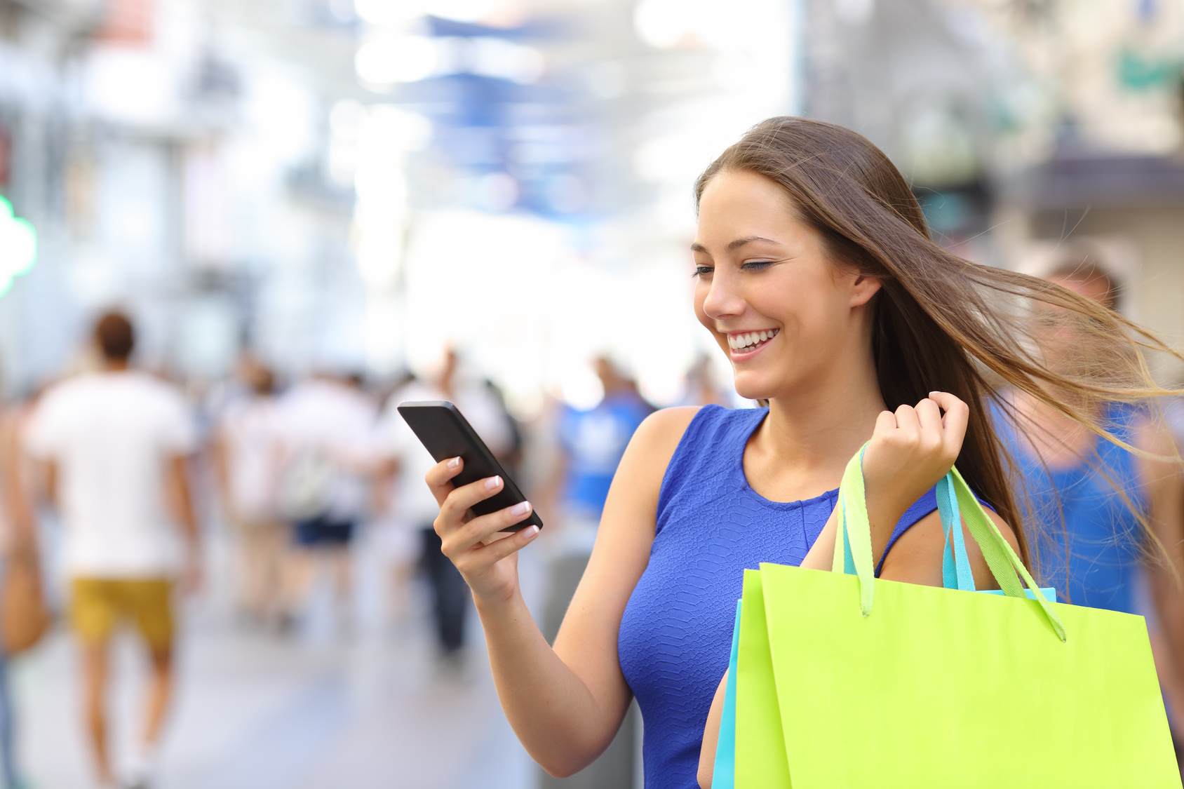 Shopper woman shopping with a smartphone in a commercial street